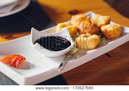 Deep-fried mozzarella cheese served with blueberry jam and strawberry slice. Shallow depth of field