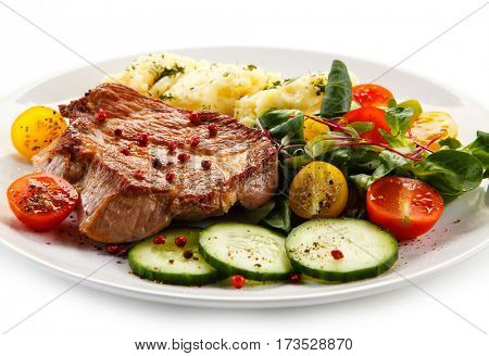 Grilled steaks, mashed potatoes and vegetable salad on white background