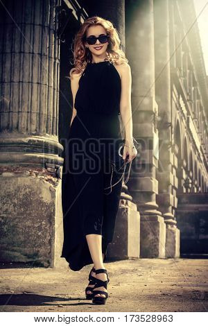 Fashionable young woman in a city center. Beautiful blonde girl in long black dress. Sepia.