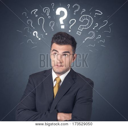 Young businessman with white question marks above his head