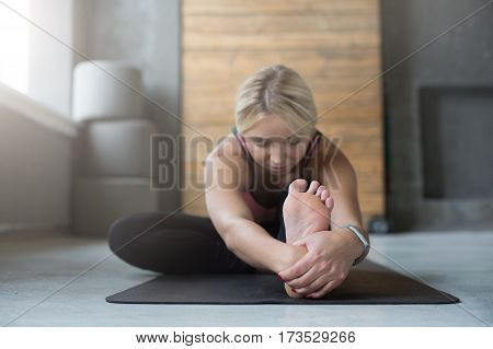 Young slim blond woman in yoga class making asana exercises. Girl do sitting forward bend pose. Healthy lifestyle in fitness club. Stretching. Selective focus on leg heel