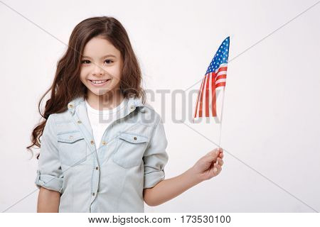 Proud to be the citizen of this country. Joyful delighted cheerful girl holding the American flag while expressing positivity and standing isolated in white background