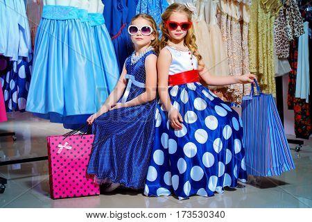 Two cute little girls go shopping. Kid's fashion. Seasonal sale, shopping.
