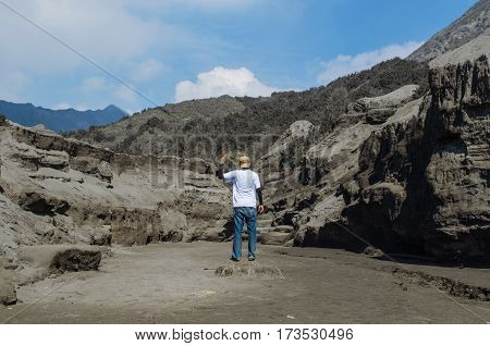 Traveler standing and wagging his finger at Bromo Mountain, Tengger Semeru national park, East Java, Indonesia.