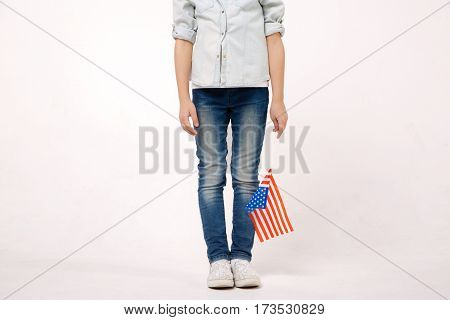 Representing my native country. Pleasant little shy child holding the American flag while expressing positive emotions and standing against white background