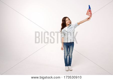 Representing multicultural country. Cheerful little shy child demonstrating the American flag while expressing positive emotions and standing against white background