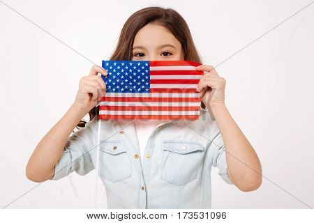 My native land. Pleasant charming child demonstrating the American flag while expressing positive emotions and standing against white background