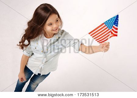 Cute little citizen. Charming beautiful delighted girl holding the American flag while expressing happiness and standing against white background