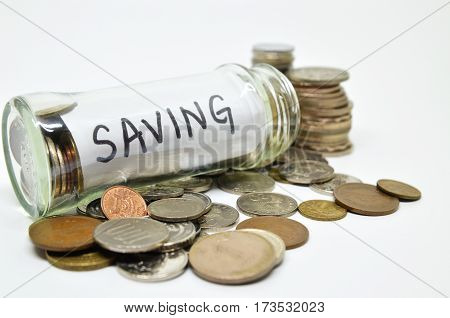 Saving Lable In A Glass Jar With Coins Spilling Out