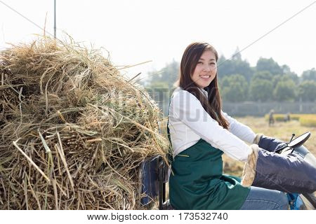 young chinese woman agronomist on motocycle with golden straw