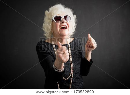 Cool grandma with her thumbs up laughing