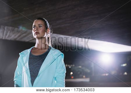 Portriat of urban female runner standing under bridge at night. Beautiful young woman standing on the street.