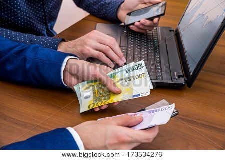 Successful Young Man Using Laptop For Sale. Concept Making Money Euro Bills.
