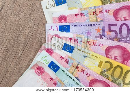 Yuan And Euro Banknotes On Wooden Background.