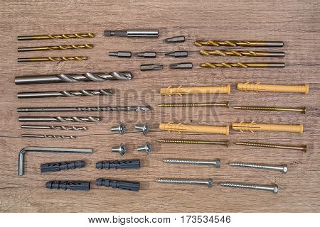 various screws and dowels on wooden desk.