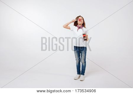 Having fun . Amused little lively girl expressing happiness and holding bottle and lollipop while standing isolated in white background
