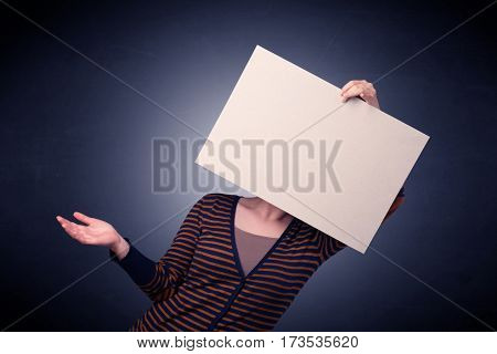 Young casual woman hiding behind a blank piece of paper