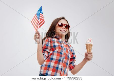 Holiday full of happiness. Artistic delighted pleasant girl expressing positivity while standing against white background and holding American flag and ice cream