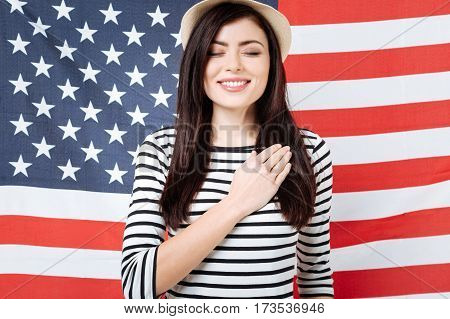 Promising love this country forever. Charismatic charming happy woman smiling and celebrating national holiday while standing with closed eyes against American flag and touching her chest