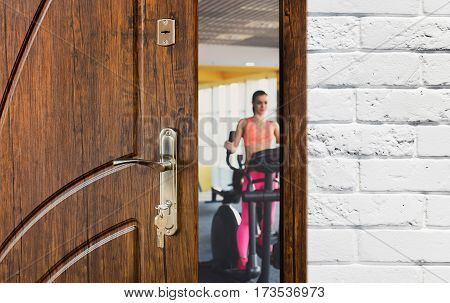 Opened door to modern gym interior with equipment. Entrance to fitness club, view of woman exercise on elliptical training. Welcome to sport, healthy lifestyle concept