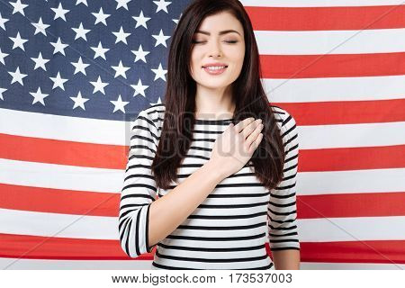 Taking an oath. Calm charming happy woman smiling and celebrating national holiday while standing with closed eyes against American flag and touching her chest