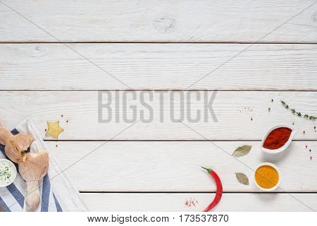 White wooden background with bread and spices. Fresh crusty bun and chili pepper with seasonings on kitchen table, free space for text or advertisement, restaurant kitchen concept