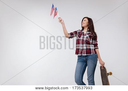Enjoy living in this country. Slim cheerful sunny woman smiling and celebrating American Independence day while standing against white background and holding American flag and skateboard