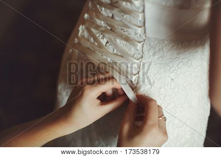 Delicate lady's hands lace up a wedding corset