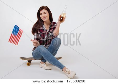 Joyful American citizenship. Sunny positive upbeat woman smiling and celebrating American Independence day while sitting against white background and holding American flag and bottle