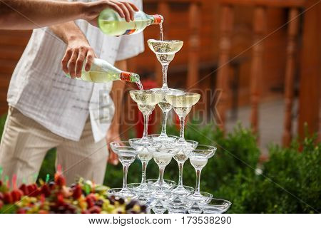 Waiters Pour Champagne On A Pyramid Of Wineglasses