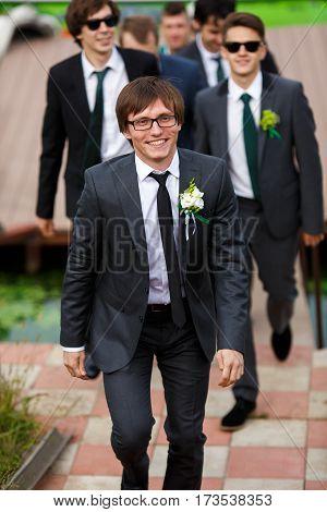 Groom and groomsmen walk together to wedding ceremony