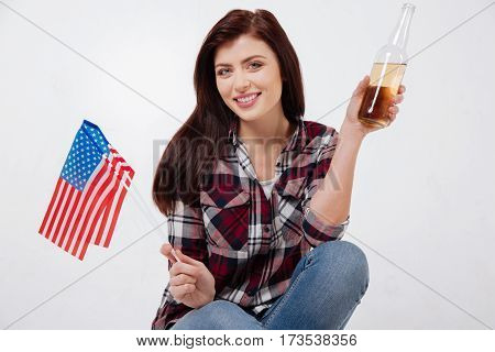 National photo session . Merry positive happy woman smiling and celebrating American Independence day while sitting against white background and holding American flag and bottle