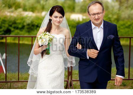 Brunette bride walks together with her father