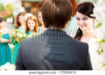 Bride looks charmed listening to the groom's oath