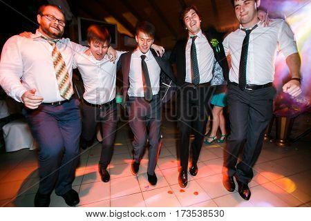 Boys in suits dance on the disco floor