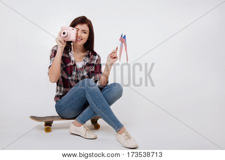 Enjoying taking photo . Gifted skilled positive woman smiling and celebrating national holiday while sitting on the skateboard against white background and holding American flag and taking photo