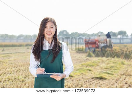 pretty chinese woman agriculture engineer in golden cereal field