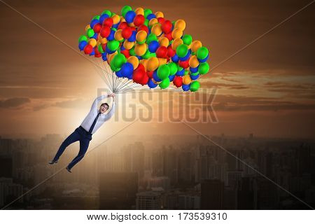 Businessman flying on balloons in challenge concept