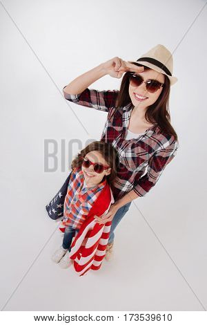 Positive family celebration. Positive stylish merry sisters celebrating American national holiday while standing isolated in white background and holding American flag