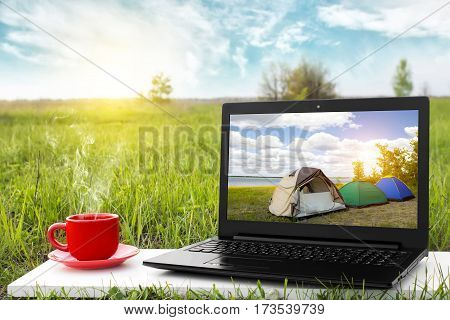Laptop and cup of hot coffee on the background picturesque nature, outdoor office. Travel concept. Business ideas. The rest of nature. Beautiful landscape.