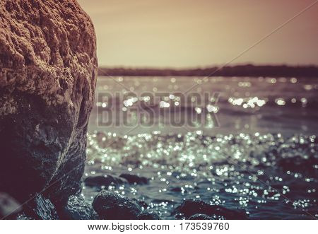 landscape, against the background of small waves of the lake a huge granite stone, it is processed, on the earth small stones, in the distance a strip of trees lie, water sparkles in the sun