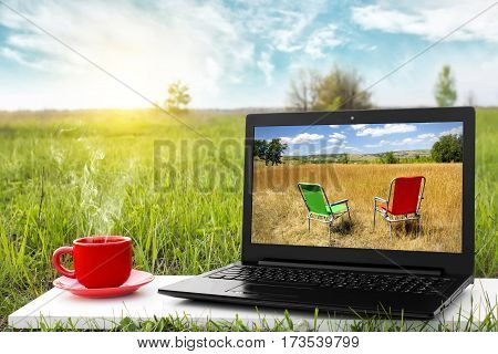 Laptop and cup of hot coffee on the background picturesque nature, outdoor office. Travel concept. Business ideas. Choice of travel. The rest of nature. Beautiful landscape.