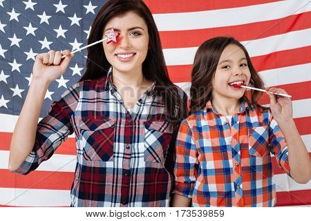 Fooling around together. Playful stylish cheerful sisters celebrating American national holiday while standing against American flag and eating lollipops