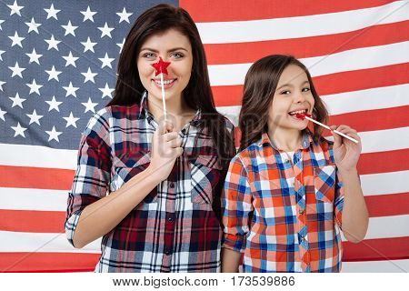 Delighted from family weekend . Playful stylish optimistic sisters celebrating American national holiday while standing against American flag and eating lollipops