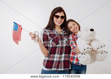 Joyful parenthood. Happy smiling cheerful mother and daughter celebrating American national holiday while standing against white background and holding flag and teddy bear