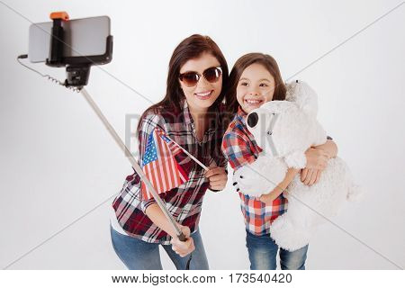 Spending funny weekend together . Joyful smiling delighted mother and daughter celebrating American national holiday while taking selfie against white background and holding flag and teddy bear
