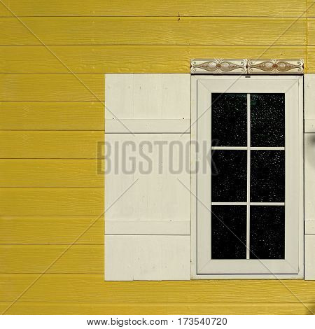 white window with black glass on wooden yellow wall