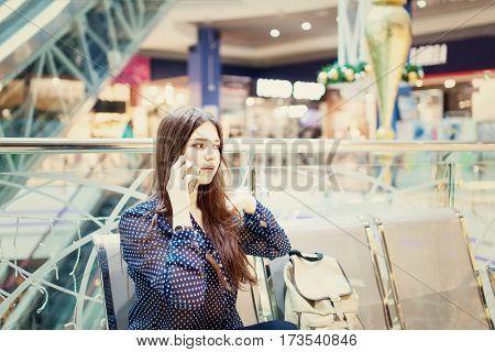 Teenage girl using mobile phone in shopping center