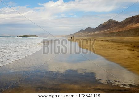 View on famous beach Cofete with silhouettes of two unknown persons walking along it beautiful water reflections yellow sand and mountains on the Canary Island Fuerteventura Spain.