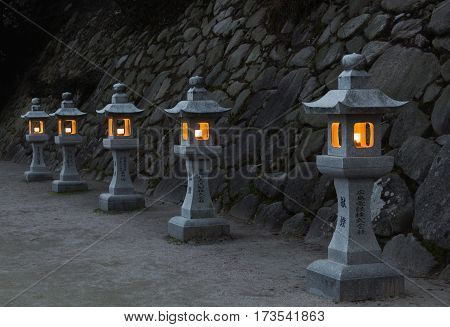 Traditional japanese stone lanterns burning in the evening